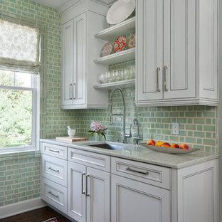 デトロイトのトラディショナルスタイルのおしゃれなキッチン (落し込みパネル扉のキャビネット、グレーのキャビネット、緑のキッチンパネル、濃色無垢フローリング、シングルシンク、御影石カウンター、磁器タイルのキッチンパネル、シルバーの調理設備) の写真