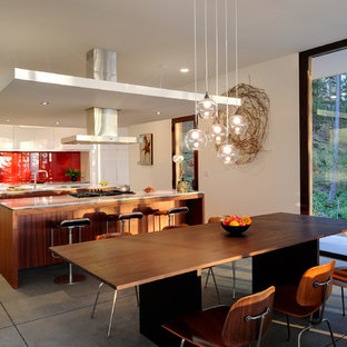 This is an example of a mid-sized contemporary galley eat-in kitchen in Seattle with flat-panel cabinets, a double-bowl sink, dark wood cabinets, solid surface benchtops, white splashback, stone slab splashback, stainless steel appliances, concrete floors and with island.