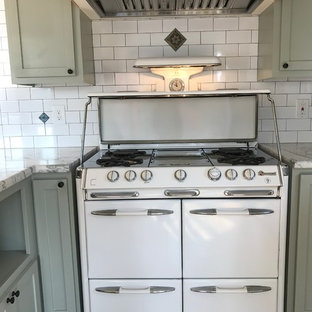 Transitional kitchen ideas - Example of a transitional medium tone wood floor kitchen design in Los Angeles with shaker cabinets, green cabinets, marble countertops, white backsplash, ceramic backsplash and white appliances