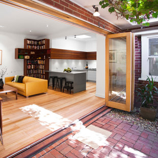 Mid-sized contemporary eat-in kitchen remodeling - Eat-in kitchen - mid-sized contemporary l-shaped light wood floor eat-in kitchen idea in Melbourne with flat-panel cabinets, green cabinets, quartz countertops, white backsplash, glass sheet backsplash and stainless steel appliances