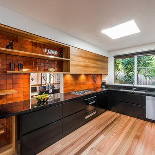 Удачное сочетание для дизайна помещения: угловая кухня в современном стиле с врезной раковиной, плоскими фасадами, черными фасадами, столешницей из кварцевого композита, оранжевым фартуком, фартуком из цементной плитки, техникой из нержавеющей стали и светлым паркетным полом без острова - самое интересное для вас