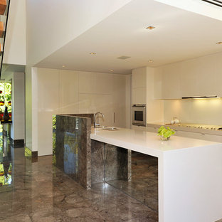 Traditional open concept kitchen appliance - Inspiration for a timeless l-shaped marble floor and gray floor open concept kitchen remodel in Melbourne with an undermount sink, marble countertops, white backsplash, glass sheet backsplash, stainless steel appliances and an island
