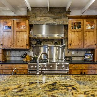 ミネアポリスの広いラスティックスタイルのおしゃれなキッチン (ダブルシンク、ガラス扉のキャビネット、中間色木目調キャビネット、御影石カウンター、グレーのキッチンパネル、セメントタイルのキッチンパネル、シルバーの調理設備、無垢フローリング) の写真