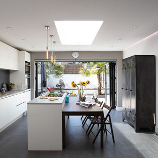 Design ideas for a large contemporary single-wall kitchen in London with an island, a submerged sink, flat-panel cabinets, white cabinets, grey splashback, stainless steel appliances, grey floors, grey worktops and glass sheet splashback.