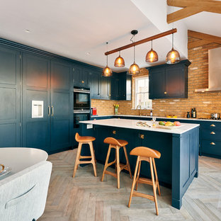 Design ideas for a large eclectic l-shaped open plan kitchen in London with an integrated sink, shaker cabinets, blue cabinets, quartz benchtops, brick splashback, panelled appliances, medium hardwood floors, with island and white benchtop.