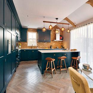 ロンドンの大きいコンテンポラリースタイルのおしゃれなキッチン (シェーカースタイル扉のキャビネット、茶色いキッチンパネル、レンガのキッチンパネル、パネルと同色の調理設備、無垢フローリング、茶色い床、一体型シンク、青いキャビネット、クオーツストーンカウンター、白いキッチンカウンター) の写真