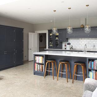 ロンドンの中サイズのインダストリアルスタイルのおしゃれなアイランドキッチン (一体型シンク、シェーカースタイル扉のキャビネット、青いキャビネット、大理石カウンター、白いキッチンパネル、セラミックタイルのキッチンパネル、シルバーの調理設備の、セラミックタイルの床) の写真