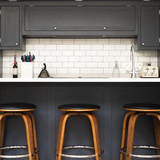 ロンドンのインダストリアルスタイルのおしゃれなキッチン (シェーカースタイル扉のキャビネット、濃色木目調キャビネット、白いキッチンパネル、セラミックタイルのキッチンパネル、黒い調理設備) の写真