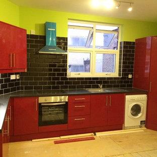 ロンドンの中サイズのコンテンポラリースタイルのおしゃれなキッチン (ドロップインシンク、フラットパネル扉のキャビネット、赤いキャビネット、ラミネートカウンター、黒いキッチンパネル、セラミックタイルのキッチンパネル、シルバーの調理設備の、淡色無垢フローリング、アイランドなし) の写真