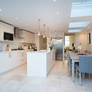 Photo of a medium sized modern single-wall kitchen/diner in London with a belfast sink, flat-panel cabinets, white cabinets, white splashback, stainless steel appliances, an island, beige floors and white worktops.