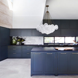 This is an example of a transitional l-shaped kitchen in Sydney with an undermount sink, shaker cabinets, blue cabinets, white splashback, window splashback, stainless steel appliances, with island, grey floor and blue benchtop.
