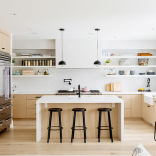 This is an example of a contemporary u-shaped kitchen/diner in Vancouver with a belfast sink, flat-panel cabinets, light wood cabinets, white splashback, stainless steel appliances, light hardwood flooring, an island, beige floors and yellow worktops.