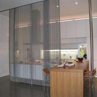 Modelo de cocina de galera, moderna, cerrada, con encimera de madera, armarios con paneles lisos y puertas de armario blancas