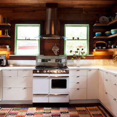 Inspiration for a mid-sized eclectic u-shaped dark wood floor eat-in kitchen remodel in Austin with a double-bowl sink, flat-panel cabinets, white cabinets, white backsplash, stainless steel appliances, laminate countertops and a peninsula