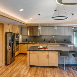 Свежая идея для дизайна: большая п-образная кухня-гостиная в белых тонах с отделкой деревом в стиле модернизм с врезной раковиной, плоскими фасадами, светлыми деревянными фасадами, столешницей из кварцевого агломерата, серым фартуком, фартуком из каменной плиты, техникой из нержавеющей стали, полом из винила, островом, коричневым полом, серой столешницей, сводчатым потолком и правильным освещением - отличное фото интерьера