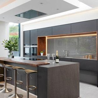 Новый формат декора квартиры: большая параллельная кухня-гостиная в стиле модернизм с островом, плоскими фасадами, черными фасадами, серым фартуком, фартуком из стекла, черной техникой и серым полом