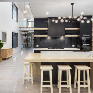 Contemporary galley open plan kitchen in Brisbane with an undermount sink, flat-panel cabinets, black cabinets, black splashback, black appliances, with island, beige floor and white benchtop.
