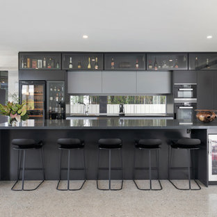 Photo of a large contemporary galley separate kitchen in Wollongong with black cabinets, with island, flat-panel cabinets, black appliances, beige floor and black benchtop.