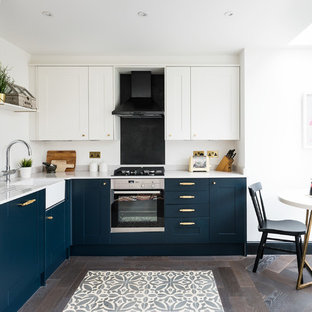 Medium sized traditional l-shaped kitchen/diner in London with a belfast sink, recessed-panel cabinets, blue cabinets, dark hardwood flooring, brown floors and black appliances.