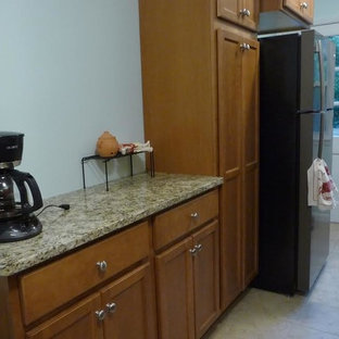 フィラデルフィアの小さいトラディショナルスタイルのおしゃれなキッチン (アンダーカウンターシンク、落し込みパネル扉のキャビネット、中間色木目調キャビネット、御影石カウンター、ベージュキッチンパネル、黒い調理設備、セラミックタイルの床、ベージュの床、磁器タイルのキッチンパネル、ベージュのキッチンカウンター) の写真