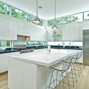 Example of a trendy l-shaped light wood floor kitchen design in New York with flat-panel cabinets, white cabinets and an island