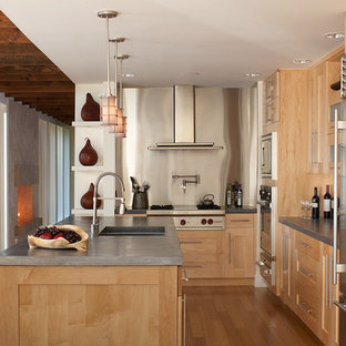 Design ideas for a mid-sized contemporary l-shaped open plan kitchen in New York with shaker cabinets, light wood cabinets, concrete benchtops, grey splashback, stainless steel appliances, with island, an undermount sink, metal splashback and light hardwood floors.