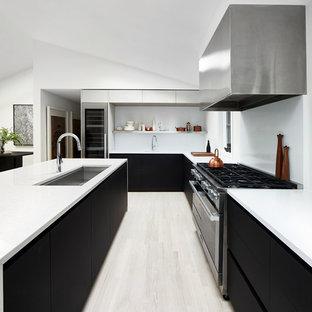 Diseño de cocina en U, minimalista, de tamaño medio, abierta, con fregadero bajoencimera, armarios con paneles lisos, puertas de armario negras, salpicadero blanco, electrodomésticos de acero inoxidable, suelo de madera clara, una isla, suelo beige y encimera de cuarzo compacto