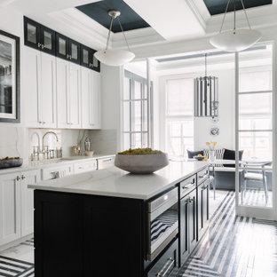 Modelo de cocina de galera, contemporánea, con fregadero bajoencimera, armarios estilo shaker, puertas de armario blancas, salpicadero blanco, electrodomésticos de acero inoxidable, una isla, suelo multicolor y encimeras blancas