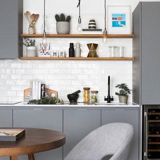 Medium sized contemporary single-wall kitchen/diner in London with flat-panel cabinets, grey cabinets, white splashback, metro tiled splashback, dark hardwood flooring, brown floors, white worktops and a submerged sink.
