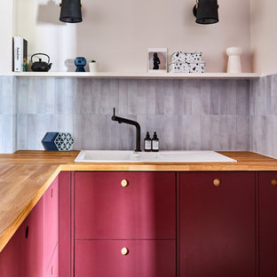 Contemporary l-shaped kitchen in London with a built-in sink, flat-panel cabinets, red cabinets, wood worktops, grey splashback, multi-coloured floors and brown worktops.