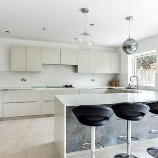 Inspiration for a contemporary u-shaped kitchen in London with a built-in sink, flat-panel cabinets, beige cabinets, white splashback, stainless steel appliances, a breakfast bar, beige floors and white worktops.