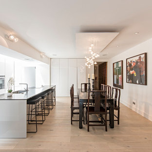 Medium sized contemporary single-wall open plan kitchen in London with a submerged sink, flat-panel cabinets, white cabinets, stainless steel appliances, light hardwood flooring, an island and beige floors.