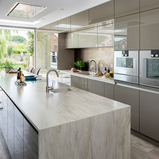 Photo of a mid-sized contemporary galley kitchen in Other with flat-panel cabinets, grey cabinets, solid surface benchtops, glass sheet splashback, stainless steel appliances, porcelain floors, with island, multi-coloured floor, beige benchtop, an integrated sink and beige splashback.