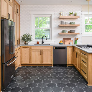 Transitional eat-in kitchen pictures - Transitional u-shaped gray floor eat-in kitchen photo in Nashville with an undermount sink, shaker cabinets, medium tone wood cabinets, white backsplash, black appliances, a peninsula and gray countertops