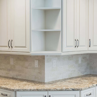 This is an example of a medium sized galley kitchen/diner in New York with a submerged sink, raised-panel cabinets, white cabinets, granite worktops, beige splashback, stainless steel appliances, plywood flooring, an island and beige floors.