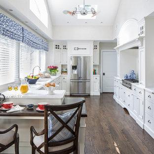Esempio di una cucina a U classica con lavello sottopiano, ante con riquadro incassato, ante bianche, top in marmo, paraspruzzi bianco, elettrodomestici in acciaio inossidabile e parquet scuro