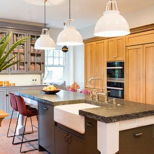 フィラデルフィアの広いトランジショナルスタイルのおしゃれなキッチン (エプロンフロントシンク、フラットパネル扉のキャビネット、白いキャビネット、ステンレスカウンター、青いキッチンパネル、セラミックタイルのキッチンパネル、シルバーの調理設備、テラコッタタイルの床、赤い床、マルチカラーのキッチンカウンター) の写真