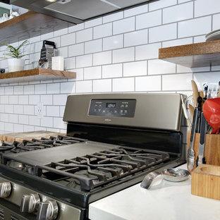 Zweizeilige, Große Stilmix Wohnküche mit Landhausspüle, flächenbündigen Schrankfronten, blauen Schränken, Quarzwerkstein-Arbeitsplatte, Küchenrückwand in Weiß, Rückwand aus Metrofliesen, bunten Elektrogeräten, Laminat, Kücheninsel, grauem Boden und weißer Arbeitsplatte in Houston
