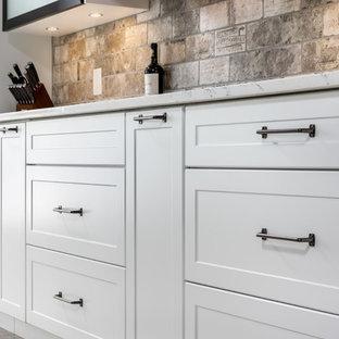Idee per una cucina design di medie dimensioni con lavello sottopiano, ante in stile shaker, ante bianche, top in granito, paraspruzzi grigio, paraspruzzi in travertino, elettrodomestici neri, pavimento in laminato, isola, pavimento grigio e top grigio