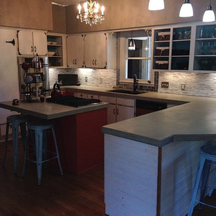 Photo of a mid-sized eclectic u-shaped eat-in kitchen in Austin with an undermount sink, flat-panel cabinets, white cabinets, concrete benchtops, multi-coloured splashback, matchstick tile splashback, stainless steel appliances, dark hardwood floors, a peninsula and brown floor.