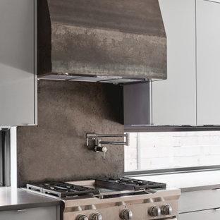 Idée de décoration pour une cuisine ouverte minimaliste avec un placard à porte plane, des portes de placard grises, un plan de travail en quartz modifié, une crédence grise, une crédence en dalle métallique, un électroménager en acier inoxydable, un îlot central et un plan de travail gris.