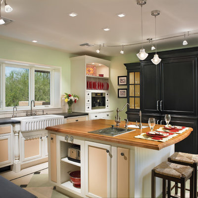 Eat-in kitchen - huge traditional u-shaped linoleum floor and beige floor eat-in kitchen idea in Phoenix with recessed-panel cabinets, a farmhouse sink, wood countertops, white backsplash and an island