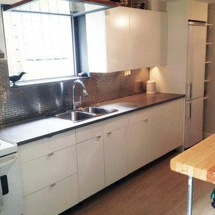 バンクーバーの小さいインダストリアルスタイルのおしゃれなキッチン (ドロップインシンク、フラットパネル扉のキャビネット、白いキャビネット、クオーツストーンカウンター、メタリックのキッチンパネル、メタルタイルのキッチンパネル、白い調理設備、クッションフロア、茶色い床、黒いキッチンカウンター) の写真