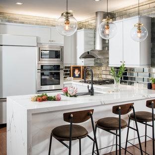 Idéer för mellanstora eklektiska vitt u-kök, med släta luckor, vita skåp, bänkskiva i kvarts, stänkskydd med metallisk yta, spegel som stänkskydd, mellanmörkt trägolv, en halv köksö, brunt golv, en undermonterad diskho och vita vitvaror