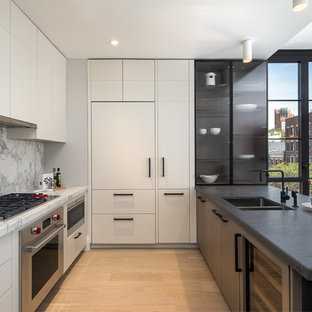 Photo of a medium sized contemporary kitchen in New York with white cabinets, marble worktops, a double-bowl sink, flat-panel cabinets, white splashback, marble splashback, stainless steel appliances, light hardwood flooring and a breakfast bar.