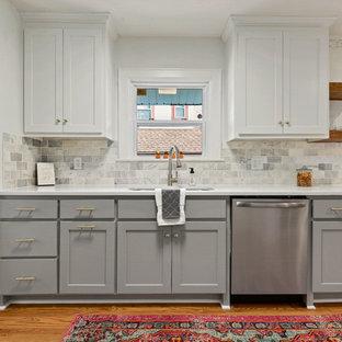 Idéer för avskilda, små vintage linjära vitt kök, med en undermonterad diskho, luckor med infälld panel, grå skåp, bänkskiva i kvarts, grått stänkskydd, stänkskydd i tunnelbanekakel, rostfria vitvaror och mellanmörkt trägolv