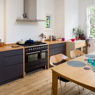 Design ideas for a contemporary single-wall kitchen/diner in London with flat-panel cabinets, no island, black appliances, light hardwood flooring, black cabinets and wood worktops.