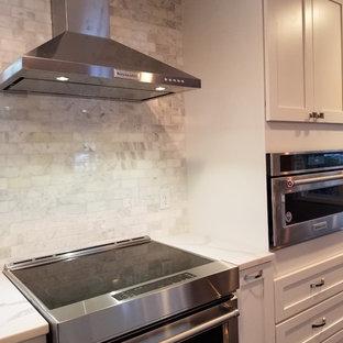 Idéer för att renovera ett mellanstort vintage kök och matrum, med en rustik diskho, skåp i shakerstil, vita skåp, bänkskiva i kvarts, vitt stänkskydd, stänkskydd i marmor, rostfria vitvaror, bambugolv, en köksö och svart golv