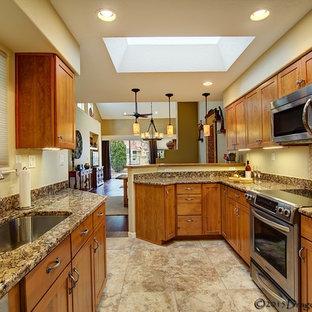 アルバカーキの小さいサンタフェスタイルのおしゃれなII型キッチン (シングルシンク、シェーカースタイル扉のキャビネット、御影石カウンター、茶色いキッチンパネル、石スラブのキッチンパネル、シルバーの調理設備の、磁器タイルの床) の写真