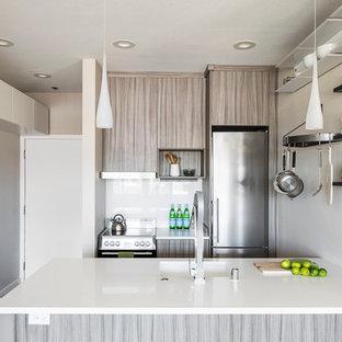 Diseño de cocina comedor de galera, minimalista, pequeña, sin isla, con fregadero bajoencimera, armarios con paneles lisos, puertas de armario marrones, encimera de cuarcita, salpicadero blanco, electrodomésticos de acero inoxidable y suelo de corcho